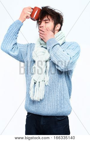 Handsome Bearded Yawning Man With Cup In Sweater And Scarf
