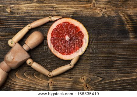Wooden Puppet Holding Grapefruit Slices