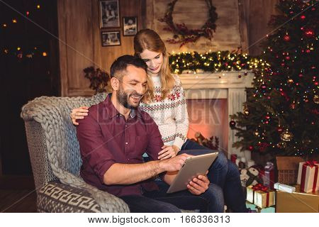 Happy couple using digital tablet while sitting in grey armchair at christmastime