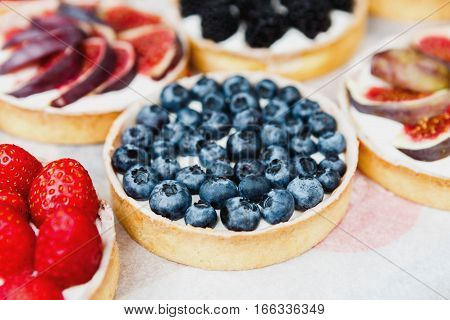 Fruit and berry tarts dessert tray assorted. Closeup of beautiful delicious pastry sweets with fresh natural blueberries and figs. French Bakery catering. Filtered, shallow depth of field