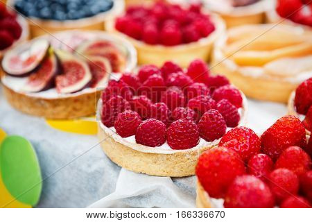 Fruit and berry tarts dessert tray assorted. Closeup of beautiful delicious pastry sweets with fresh natural raspberries, strawberries and figs. French Bakery catering. Shallow depth of field