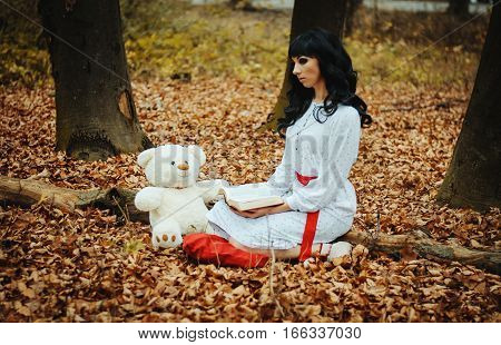Young Sad Lonely Brunette Girl At Sleepwear Sitting On Autumn Forest And Read Book Near Soft Toy Bea