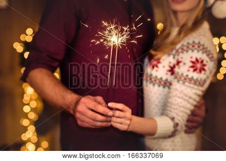 Partial view of young couple holding sparklers