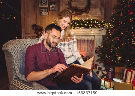 Smiling young couple reading book at christmastime