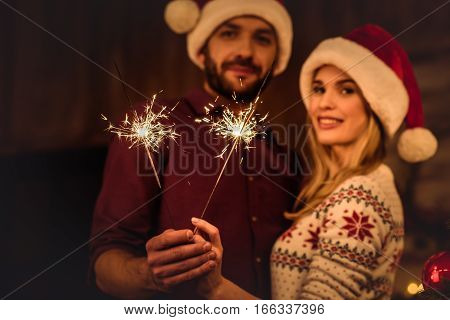 Young couple in santa hats holding sparklers