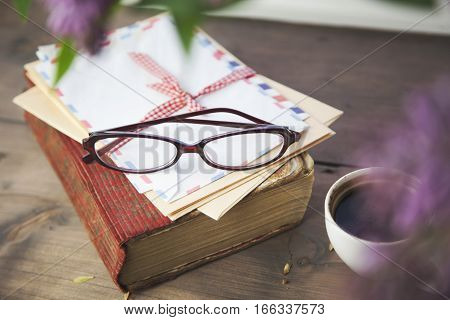 cup of coffee wite lettersbookglasses and flower