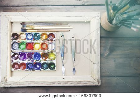 Box of watercolor and brushes on wooden table