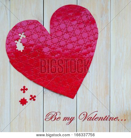 Red heart shaped puzzle on white wooden background. Concept for Love or St Valentines day