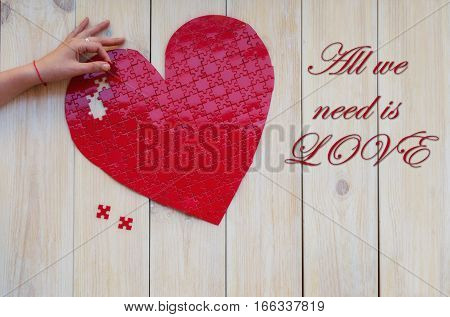Hand assembling red heart shaped puzzle on white wooden background. Concept for Love or St Valentines day