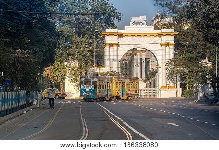 KOLKATA, INDIA -JANUARY 22, 2017: Heritage Kolkata tram passing the front entrance of historic and Gothic architectural Governor house near Dalhousie Chowringhee area, Kolkata.