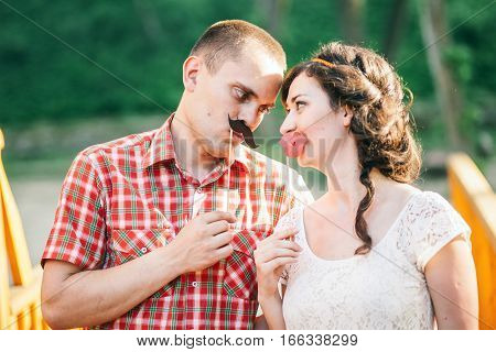 couple with paper moustache. Couple have fun and joy.
