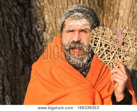 Frozen smiling man with squinty eyes bearded hipster with beard and moustache covered with white frost wrapped in orange blanket with wicker heart on winter day outdoors on natural background