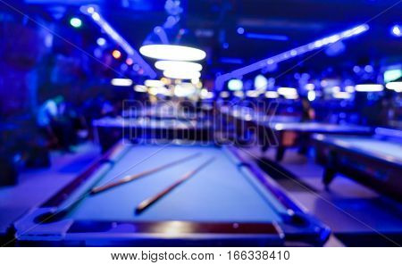 Defocused background of billiard playroom - Blurred composition of pool game saloon with dominant blue color tones and incandescent neon light - Fun and entertainment concept with blurry dark backdrop