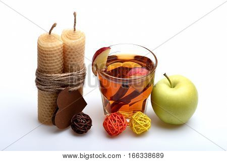 hot drink of apple tea with cinnamon spice stick or mulled wine in glass honeycomb wax candle with valentines day heart on rope and decorative straw balls isolated on white background