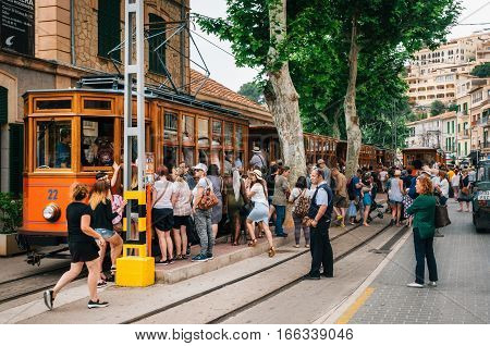 Port de Soller Mallorca Spain - May 26 2016: A crowd of tourists get on the old vintage tram service going from Port de Soller resort to Soller. Landmark of Majorca