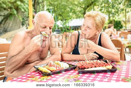 Senior couple having fun eating seasonal fruit in thai restaurant bar outdoors - Mature man and woman on active elderly vacation - Happy retirement concept with people together - Warm shadow filter