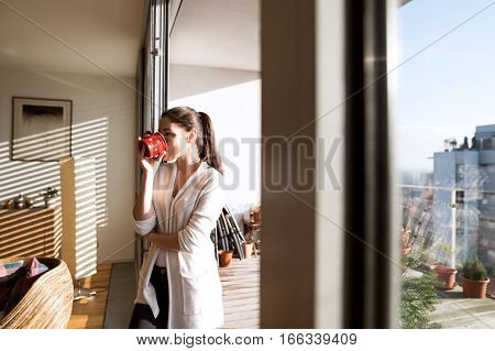 Beautiful young woman relaxing on balcony with city view holding cup of coffee or tea, drinking it