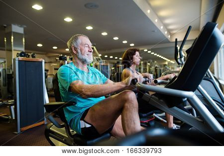 Beautiful fit senior couple in sports clothing in gym doing cardio workout, exercising on recumbent bicycle. Sport fitness and healthy lifestyle concept.