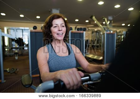 Beautiful fit senior woman in sports clothing in gym doing cardio workout, exercising on recumbent bicycle. Sport fitness and healthy lifestyle concept.
