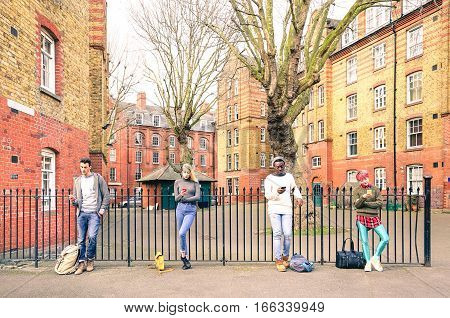 Multiracial people group and urban friends using smartphone near Shoreditch London - Technology addiction lifestyle concept with bored guys and girls texting on mobile smart phone - Warm retro filter