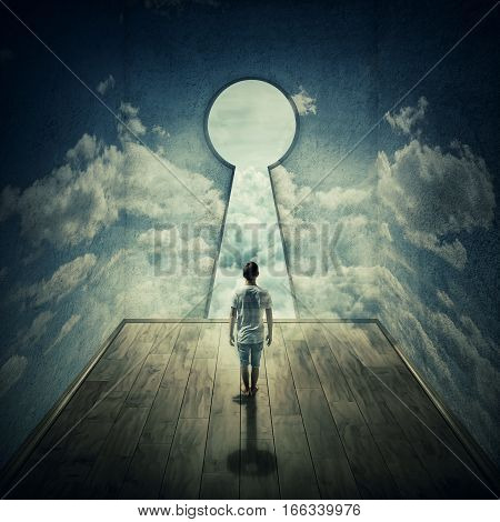Abstract idea with a person standing in front of a big keyhole doorway surrounded by limitations daily routine concrete walls with clouds texture casting a key shadow.
