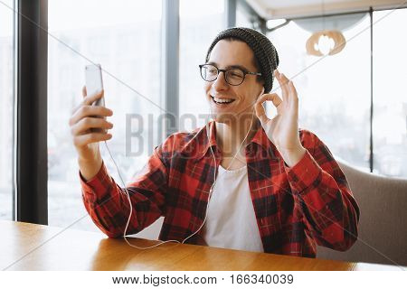 Attractive young man or freelancer is sitting in cafe during the coffee break. He is wearing hat, checkered shirt and eyeglasses. He has pleasant conversation on skype using some gestures