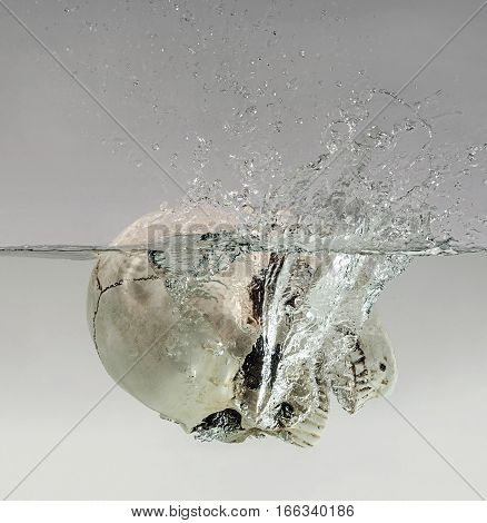 Drowning human skull in the clean water.