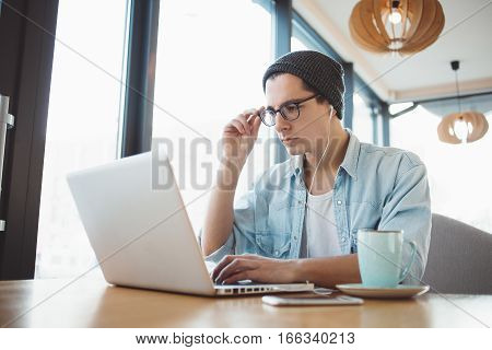 Handsome businessman in casual wear and eyeglasses is using a laptop Stylish freelancer trying to do his job sitting in cafe. He is reading some information and holding his glasses