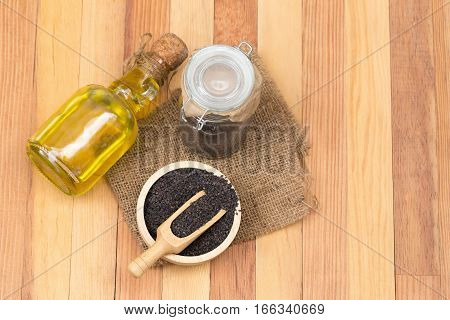Black sesame seeds and oil on wooden table