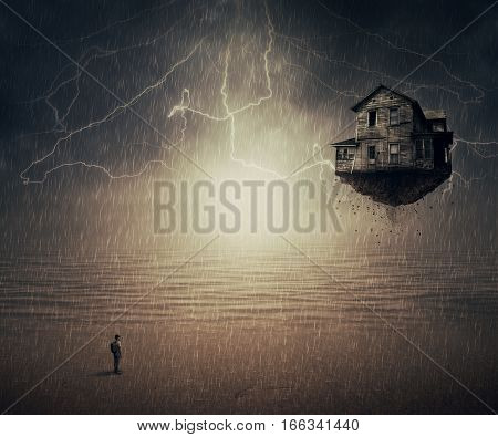 Surreal background of a man standing in the rain in front of a flying house ripped from the ground near the ocean. Sixth sense concept.
