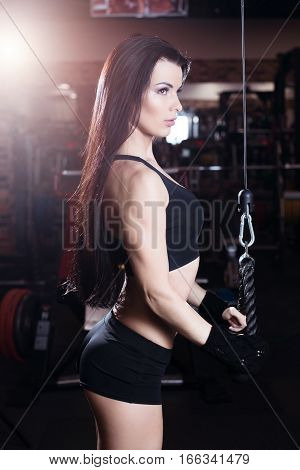 Muscular Brunette Fitness Girl Doing Exercises In The Gym. Fitness Girl Lifting Weights On A Machine