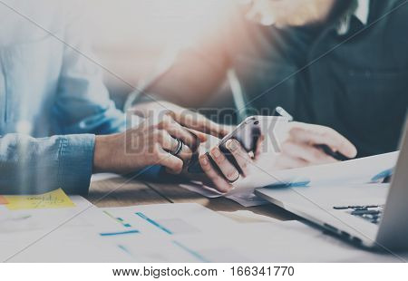 Concept of business meeting partners.Young businessman team working with new startup project in modern office.Mobile smartphone holding female hands. Horizontal, film effect