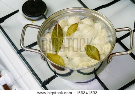 dumplings boiled in a pot on the gas stove close-up