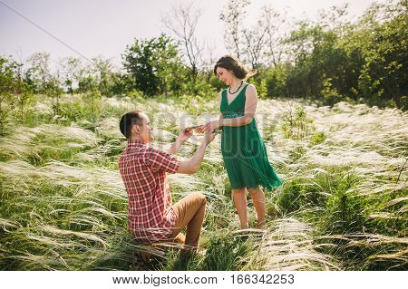 man making marriage proposal. Wedding proposal outside in meadow