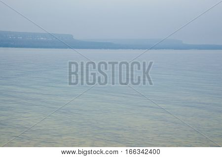 Image has the limestone escarpment cliffs in the distance with reflected yellow and blue ripples and waves in the crystal clear lake