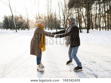 Beautiful senior woman and man in sunny winter nature ice skating.