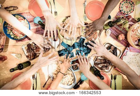 Top view of friend hands with mobile smart phones at barbecue garden party - Multiracial people group enjoying grill meal at backyard bbq - Food and tech concept outdoors - Warm desaturated filter
