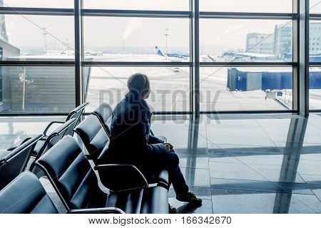 Young woman waiting at the airport and looking at window