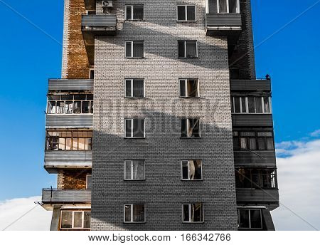 Apartment building, housing complex, social housing, apartments, residential area, fragment of building, blue sky. Strange house. Funny house.