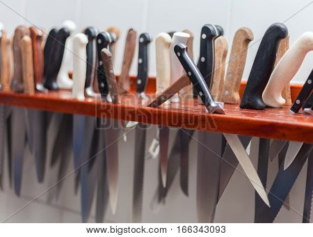 Many large knife hanging wooden storage knife in the kitchen of restaurant stock photo