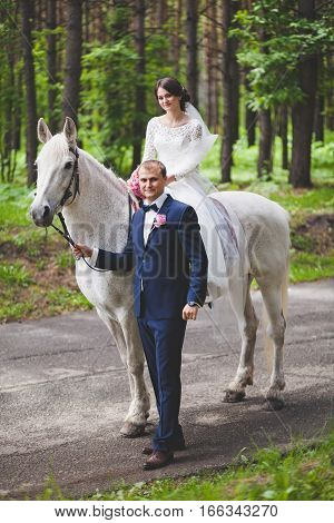 Young groom and bride with white horse in park