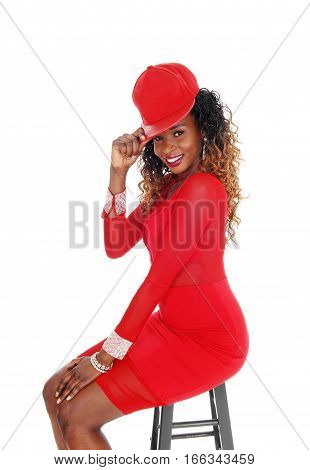 A lovely young African American woman in a tight red dress and red cap sitting in profile isolated for white background.
