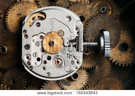 Vintage clockwork mechanism parts and hand watch macro view. rusty grunge textured metal gears background. Shallow depth of field