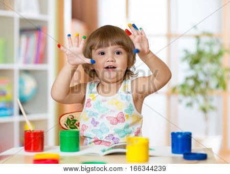 cheerful kid girl showing her fingers painted in bright colors