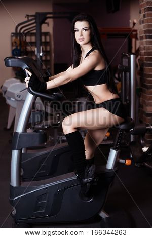 Muscular Young Woman Wearing Sportswear Training On Exercise Bikes In Gym. Intense Cardio Workout.