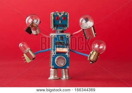 Serviceman illuminator with light bulbs in four hands. Colorful robotic character holds different retro lamps. Funny electronic parts. Red background macro