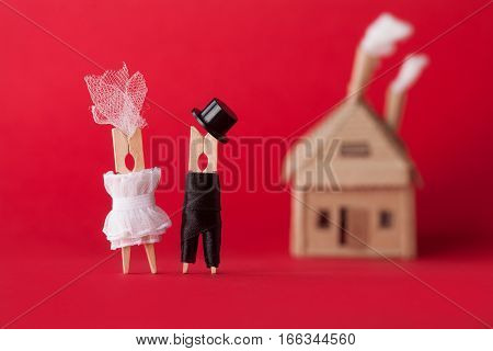Wedding invitation and love concept. Bride groom clothespin peg characters, cardboard home on red background. Abstract woman in white dress, man black suit hat. Macro view, shallow depth of field photo
