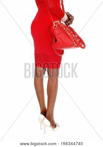 A lovely young African American woman in a tight red dress showing her butt and legs standing isolated for white background.