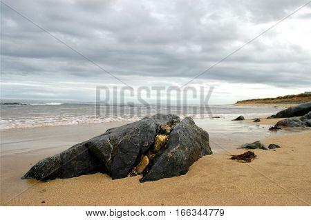 Split boulder on beach with smaller rocks filling up the crack.