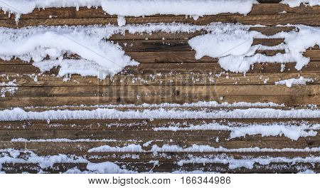 Stacked wooden boards are covered with snow.